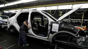 Plant employees assemble a 2011 Ford Explorer on