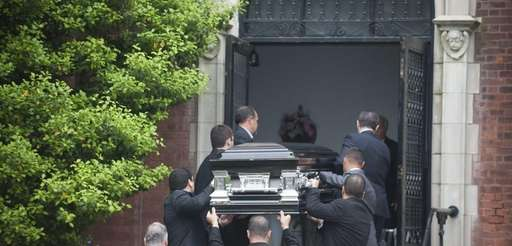 The coffin of Andrea Rebello is carried into