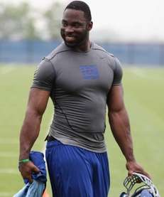 Justin Tuck walks off the field following OTAs