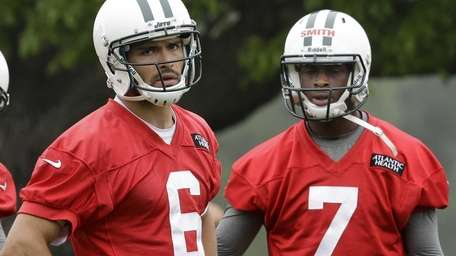 Mark Sanchez (6) and Geno Smith (7) stand