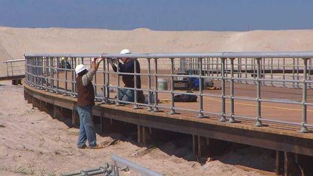 Crews work to rebuild the boardwalk at Robert