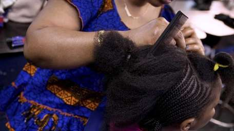 An African hairdresser braids a young woman's hair