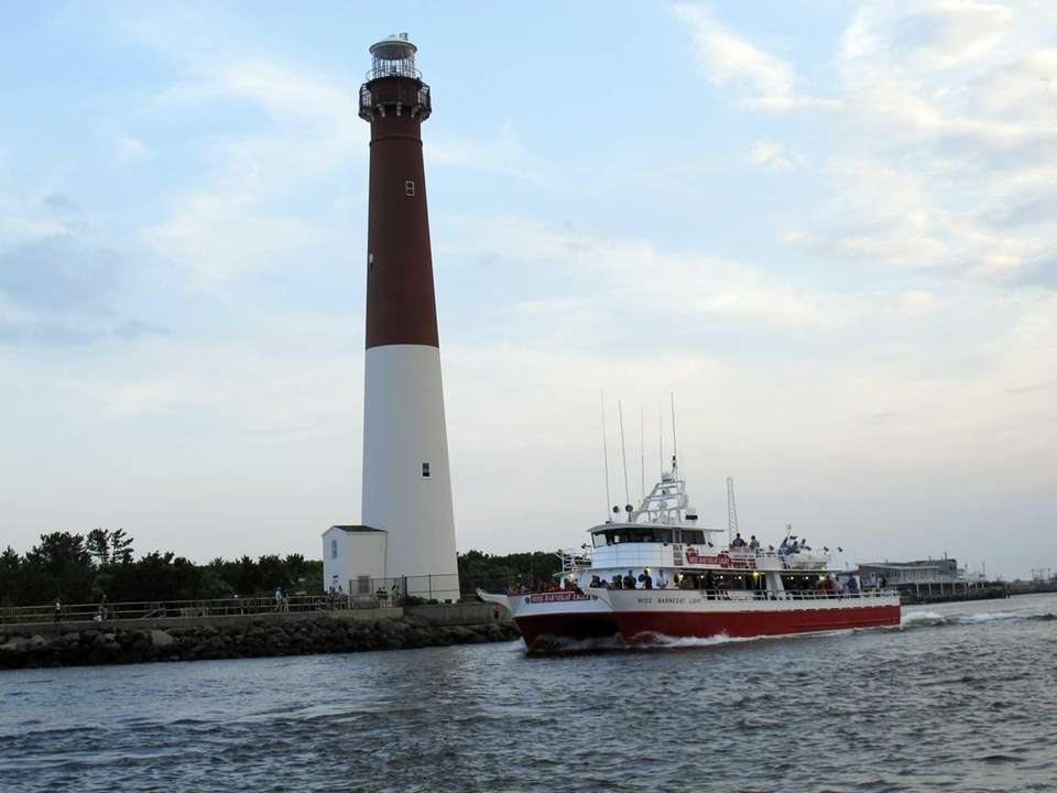 A fishing boat sails past Barnegat Lighthouse, one