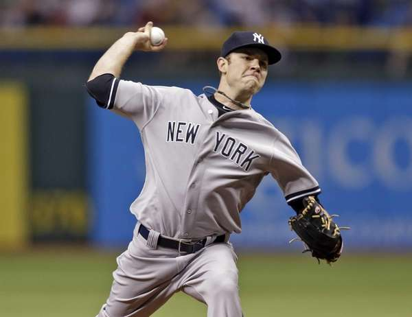 Yankees starting pitcher David Phelps delivers to Tampa
