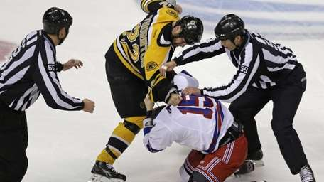 Officials try to separate Boston Bruins right wing