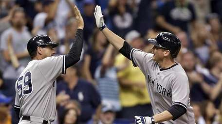 Yankees' Lyle Overbay, right, high-fives third base coach