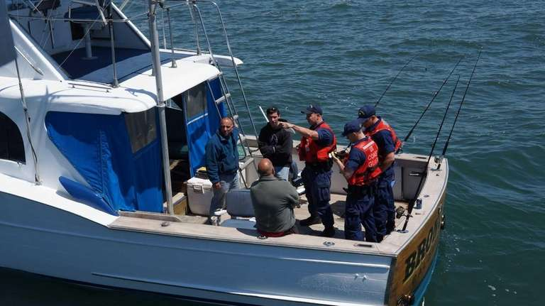 Coast Guard officers perform a safety check on