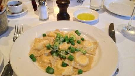 Ricotta ravioli are served with spring vegetables and