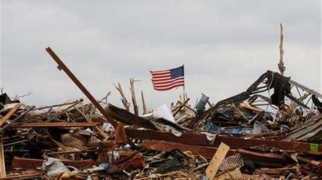 A flag continues to fly amidst the remains