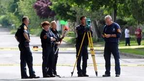 Investigators take measurements at Acorn and Cinnamon streets,