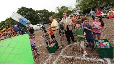 First-grader John Edom, 7, tosses a plastic water