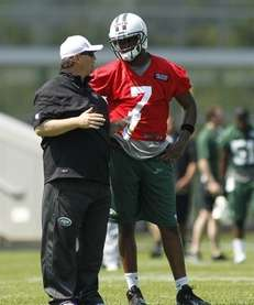 Quarterback Geno Smith speaks with offensive coordinator Marty