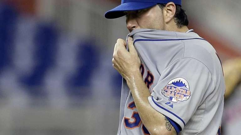 Mets' Shaun Marcum wipes his face after intentionally