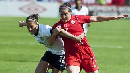 Canada's Rhian Wilkinson, right, battles for the ball