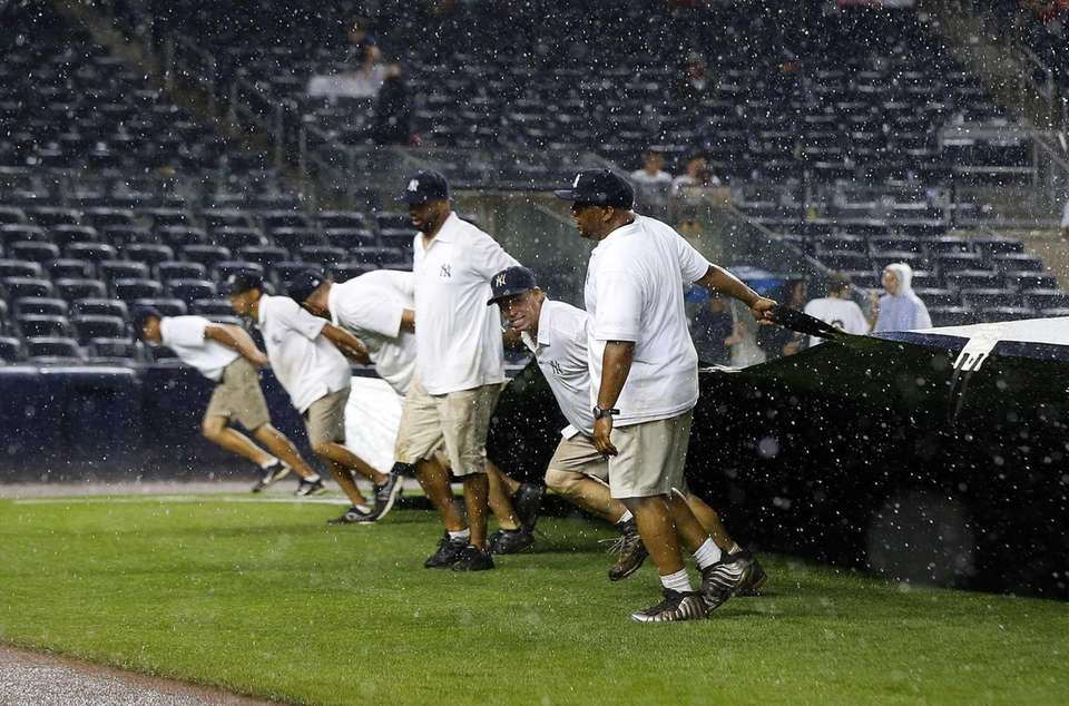 The grounds crew brings the tarp onto the