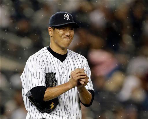 Rain falls as Hiroki Kuroda reacts after allowing