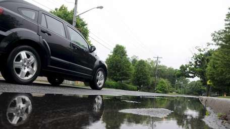 A vehicle drives by a puddle on North