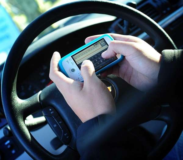 Photo illustration of texting while driving.