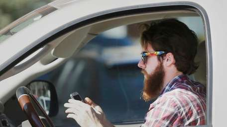 An man works his phone as he drives