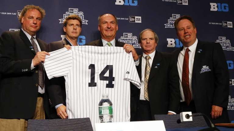 Big Ten commissioner Jim Delany, center, is presented