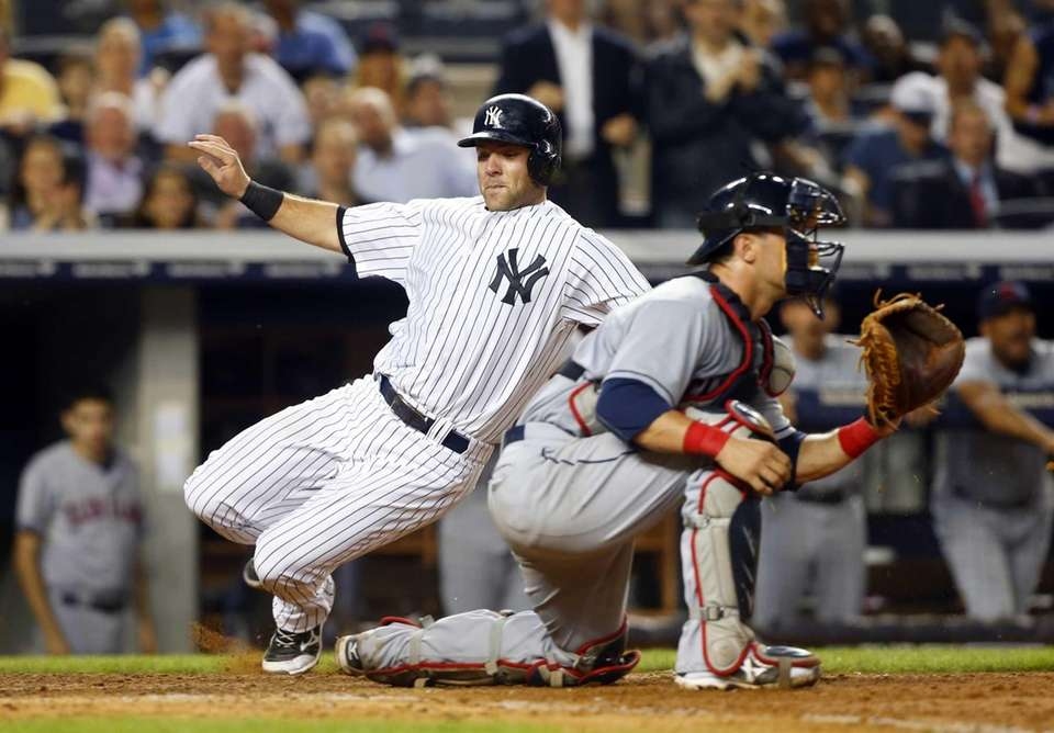 Austin Romine slides past Yan Gomes #10 of