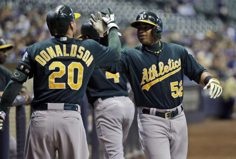 Athletics left fielder Yoenis Cespedes, right, is congratulated