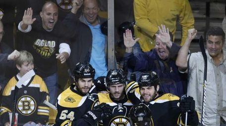 Boston Bruins center David Krejci, center, is congratulated