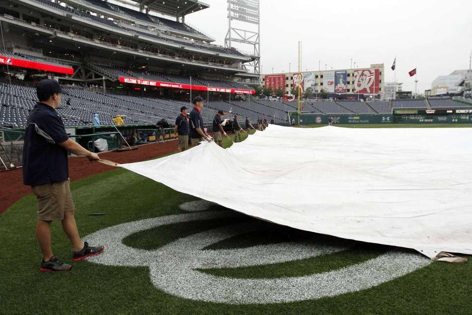 The grounds crew covers the field before a