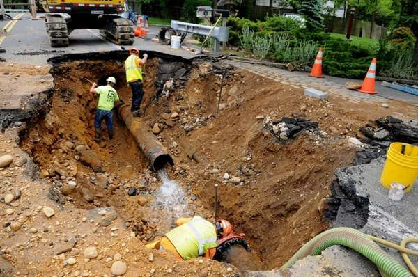Construction crews work on repairing a major water