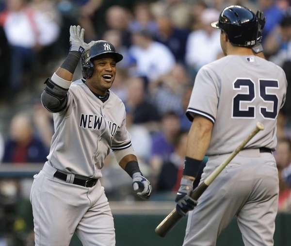Yankees' Robinson Cano, left, greets Mark Teixeira, after