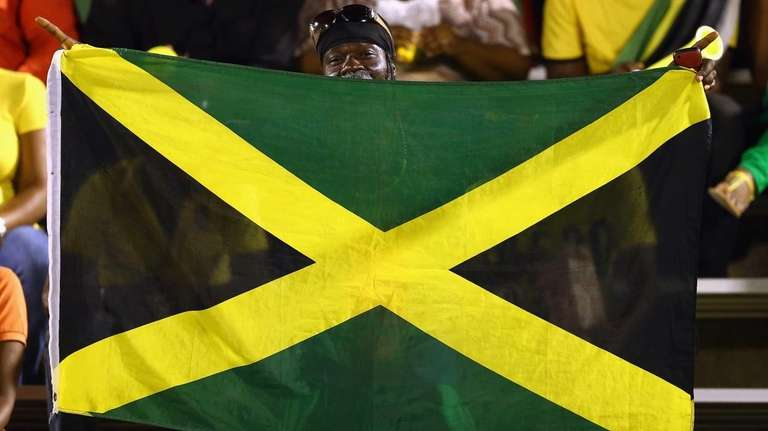 A fan waves a Jamaican flag in Kingston,