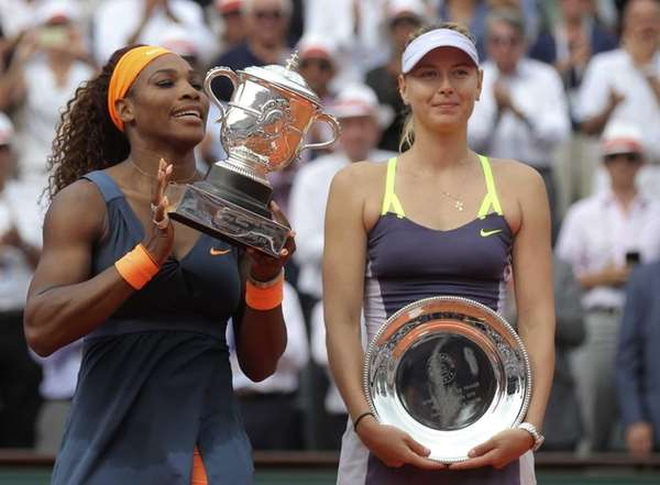 Serena Williams, left, holds the winner's cup after