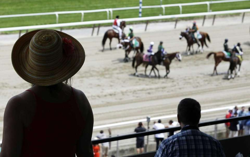 Racing fans watch as horses are led on