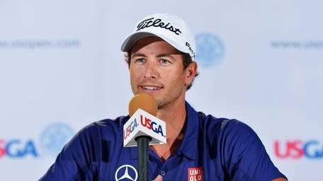 Adam Scott talks with the media during a