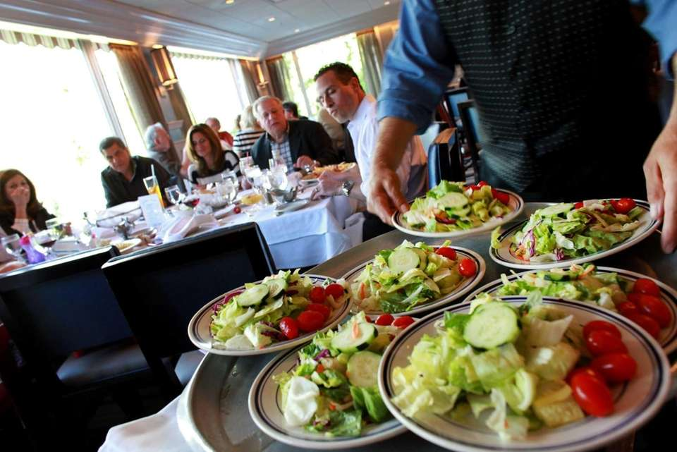 A waiter serves salads at The Jolly Fisherman