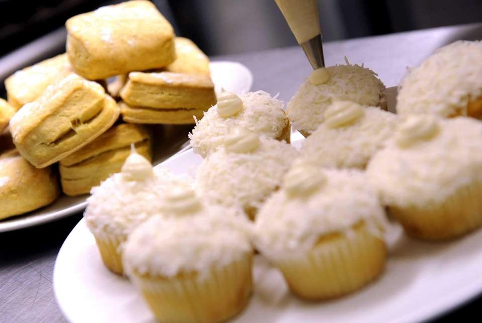 Cupcakes are topped with coconut frosting at Cook's