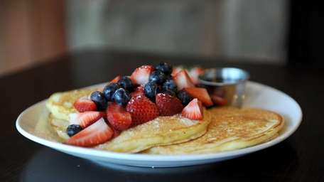 House pancakes are topped with mixed fruit at