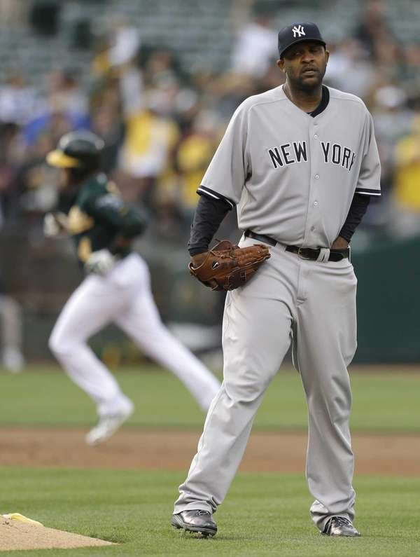 Yankees' CC Sabathia, right, waits for Oakland Athletics'