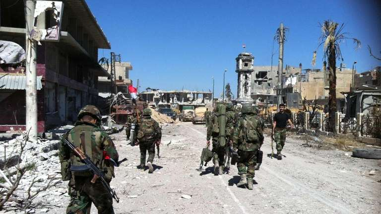 Syrian army's soldiers walk in a street left