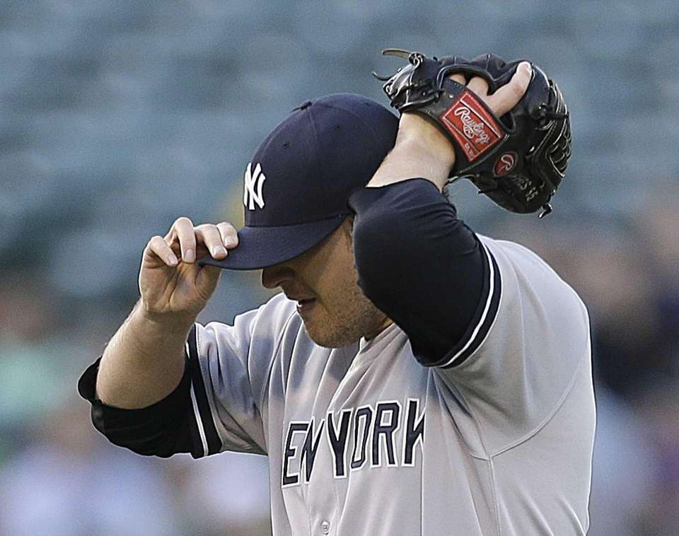 Yankees' Phil Hughes adjusts his cap after giving