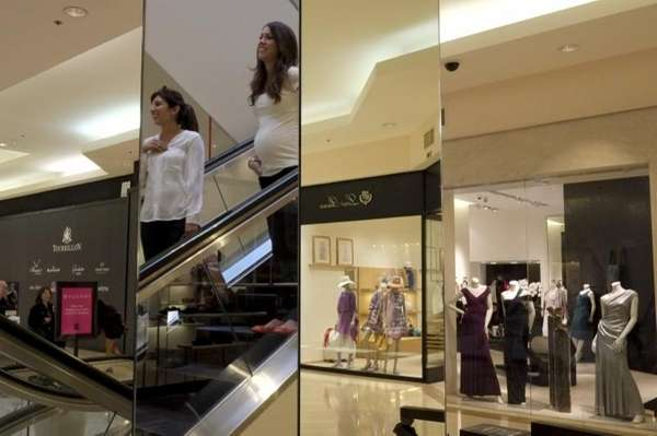 Shoppers are reflected in the mirror at a
