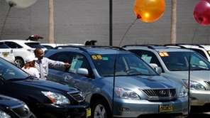 A salesman shows a certified pre-owned Lexus vehicle