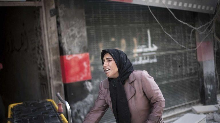 A Syrian woman cries near Dar El Shifa