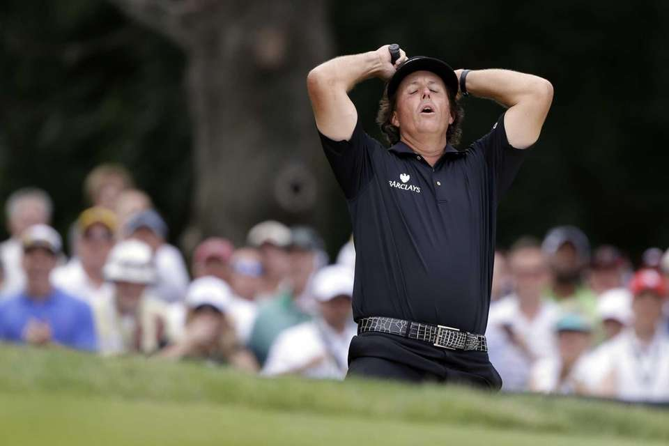 Phil Mickelson reacts after hitting out of a