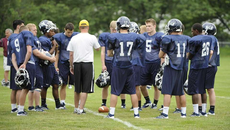 Long Island defensive players listen to instructions during
