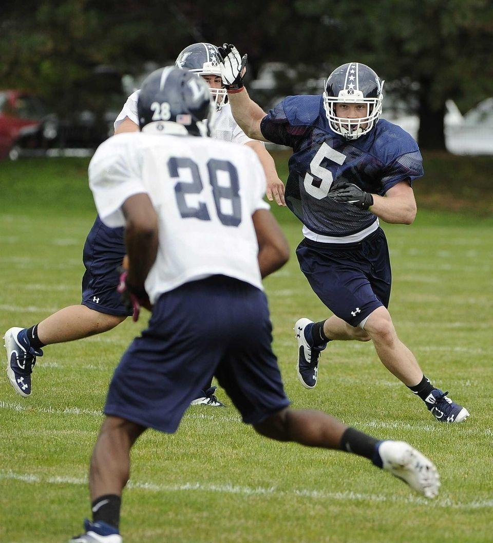 Long Island middle linebacker Steven Casali, right, defends