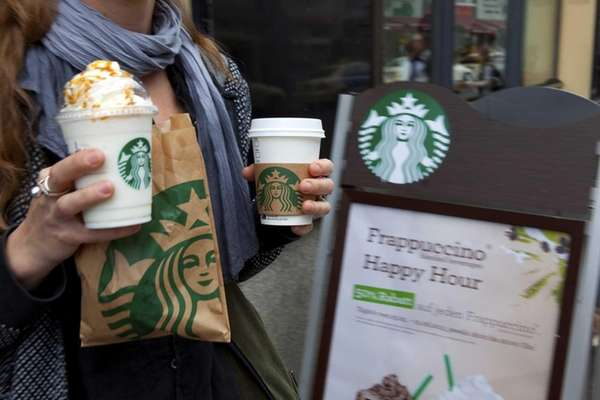 A customer holds Starbucks Corp. beverages as she
