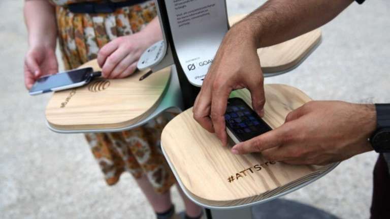 People charge their cell phones at a free