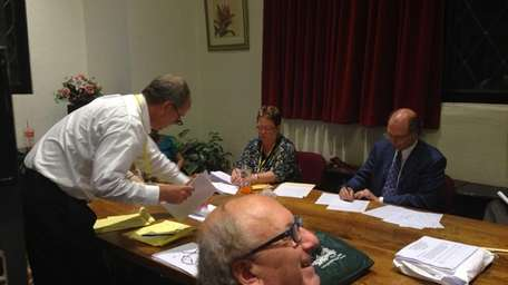 Village and election officials count write-in votes in