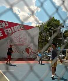 Children play on a handball court at 80th